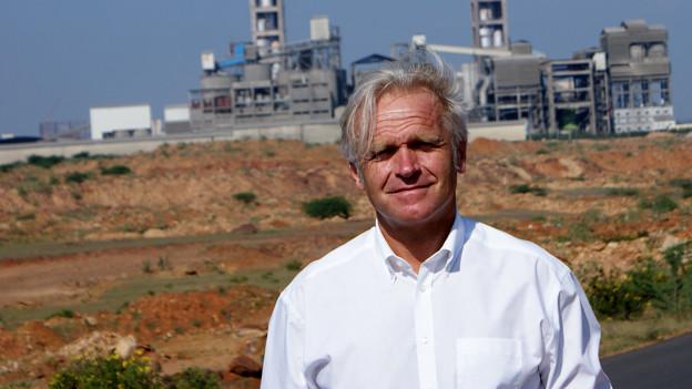 Markus Oberle steht vor einer Zementfabrik.