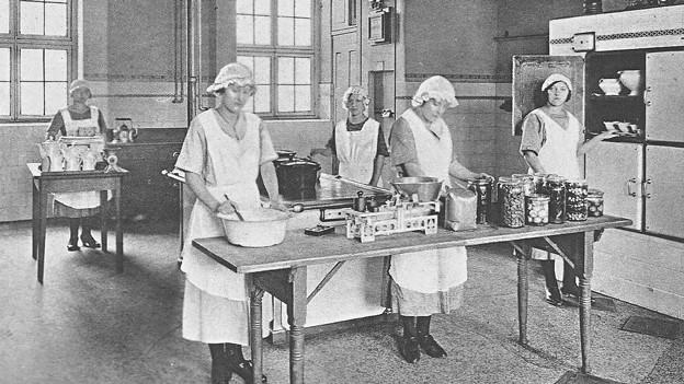 Schwarz-weiss-Aufnahme von einer Gruppe von Frauen in einer grossen Küche.