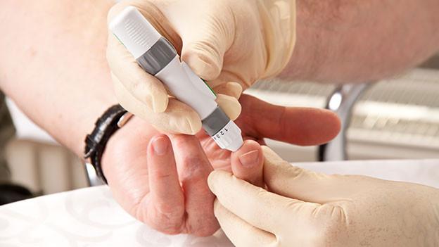Arzt nimmt Patient Blut am Finger ab.