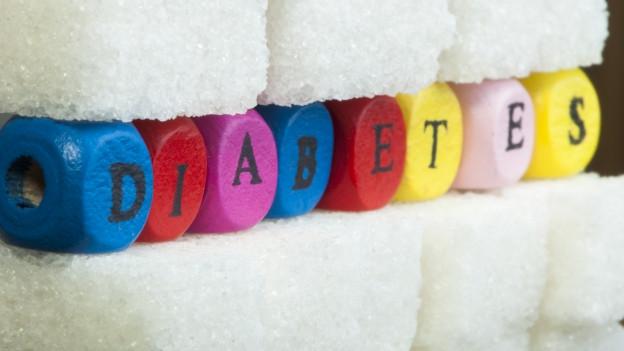 """Zwei Reihen Würfelzucker und dazwischen farbige Buchstabenwürfel, die das Wort """"Diabetes"""" bilden."""