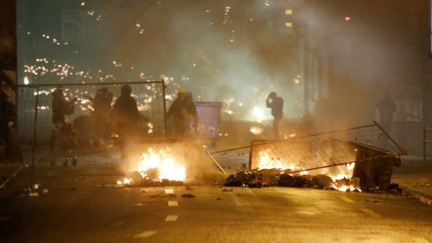 Brennende Barrikade und Polizisten vor der Berner Reitschule