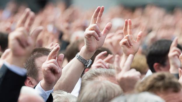 Viele Menschen strecken die Hand zum Eid in die Höhe.