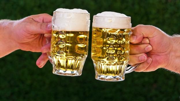 Zwei Hände halten zwei volle Bierkrüge beim Anstossen.