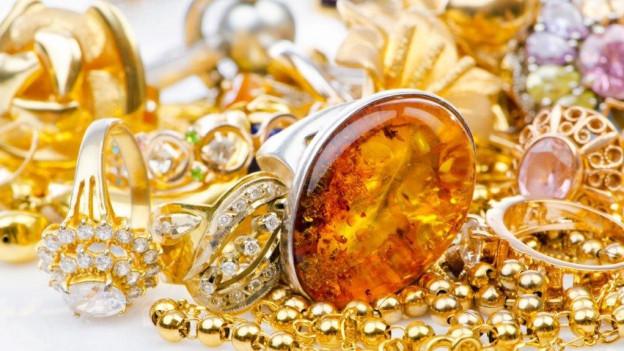 Diverse Goldringe und Goldketten auf einem Haufen.