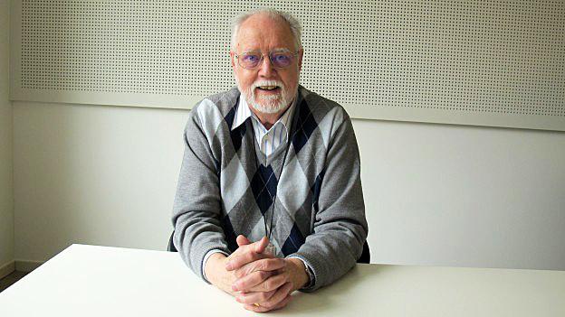 Karl Elsener sitzt in einem Raum.