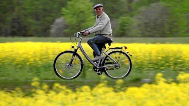 Senior fährt mit E-Bike auf einer Landstrasse. Links und rechts sind Rapsfelder.