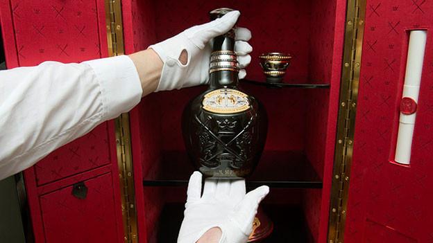 Jemand nimmt mit weissen Handschuhen eine exklusive Flasche Whisky aus einem Regal.