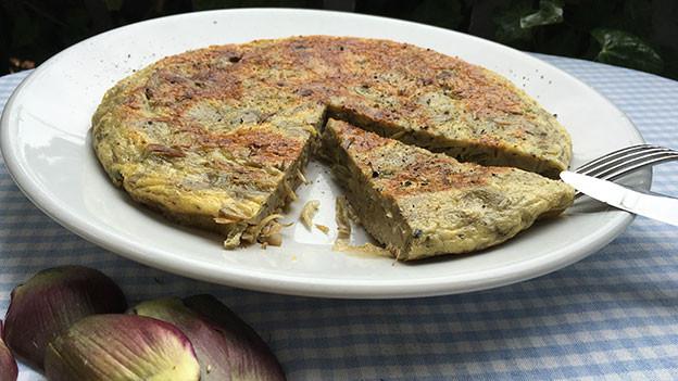 Omelettenartige Eierspeise mit Gemüse ist auf einem Teller angerichtet.