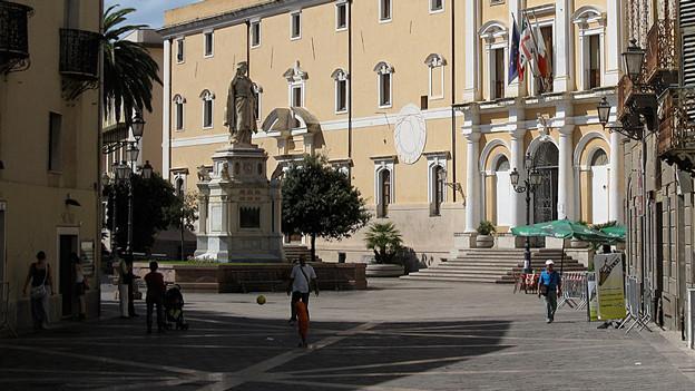 Blick auf einen Platz mit alten Gebäuden und einer Statue.
