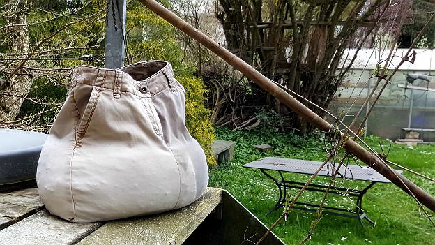 Ein mit Erde gefüllter Sack aus einer alten Hose steht auf einer Terrasse
