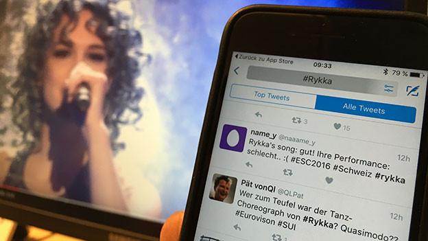Rykka auf Bildschirm und Smartphone mit Twitter vorne.