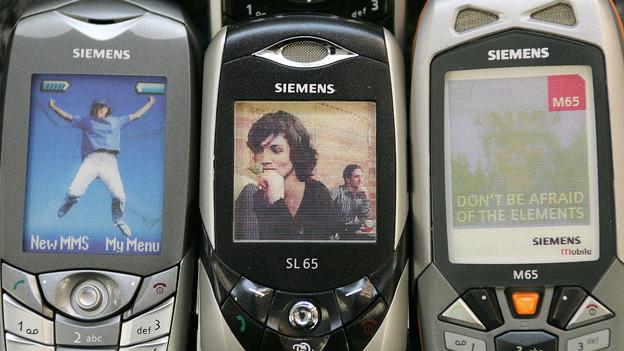 Drei alte Handys in Nahaufnahme.