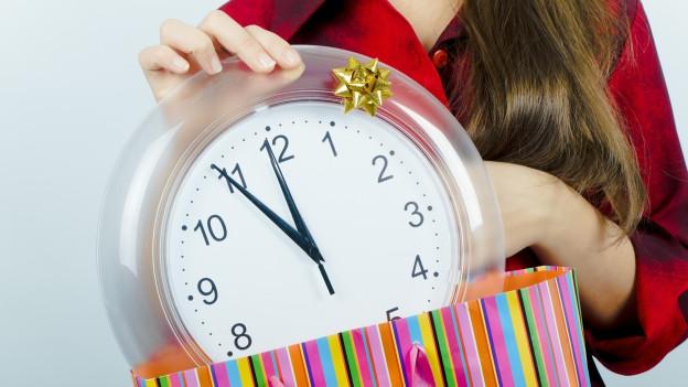 Eine Frau zieht eine grosse Uhr aus einem Geschenkpaket.