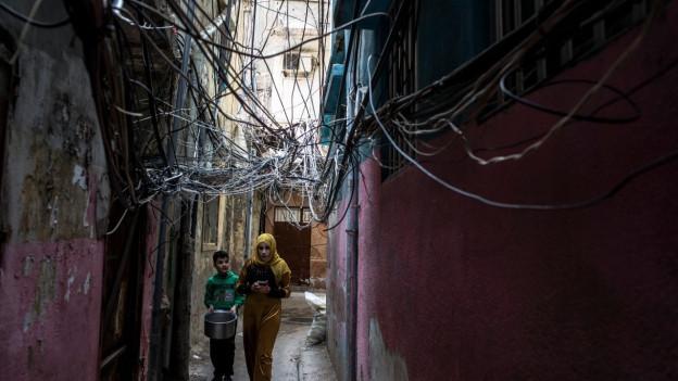 Syrische Flüchtlinge in einer engen Gasse, über ihnen ein Wirrwarr an elektrischen Leitungen