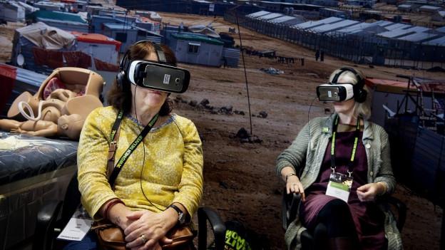Zwei Menschen sitzen auf Stühlen und tragen überdimensionierte Brillen.