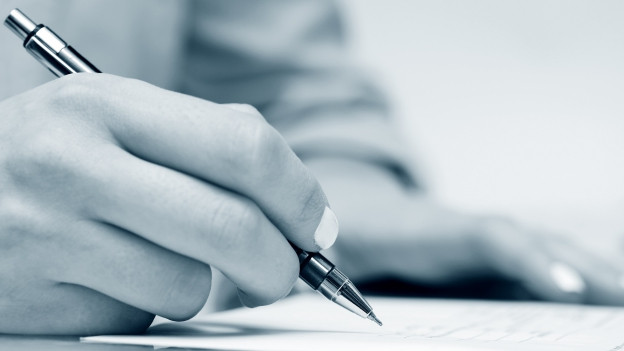 Eine Hand hält einen Stift und schreibt.