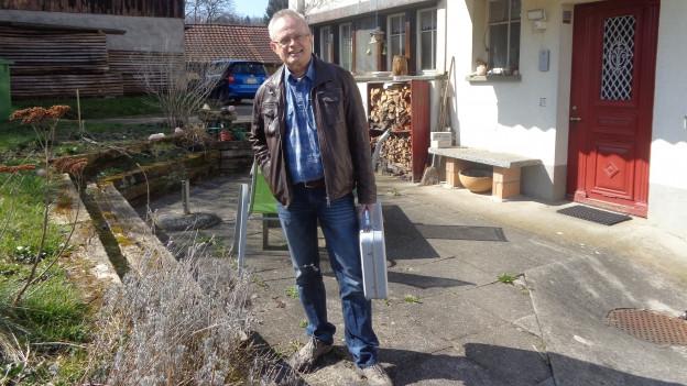 der Hausarzt Christoph Schmidli steht mit seinem Arztkoffer vor einem Bauernhaus.