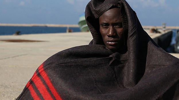 Ein Flüchtling sitzt am Boden und ist in eine Decke gehüllt.