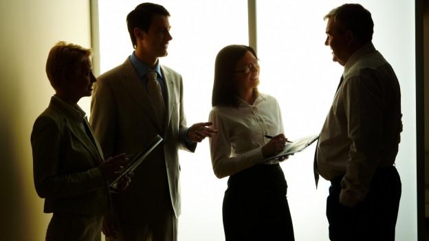 Zwei Männer und zwei Frauen stehen diskutierend zusammen.