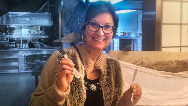 Evelyne Lüthi-Graf hält zwei Silberbesteckstücke in der Hand.