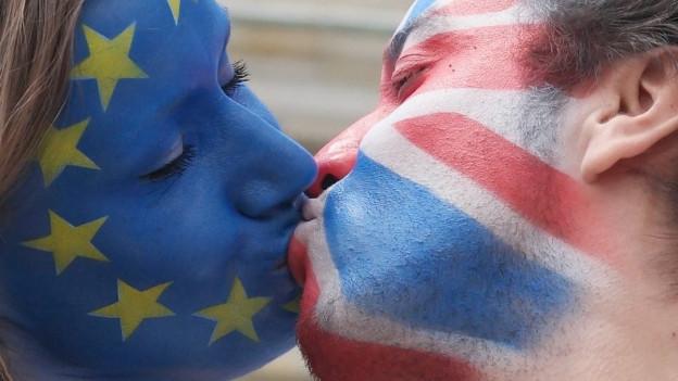Eine Frau mit aufgemalter Europaflagge küsst einen Mann mit aufgemalter Grossbritannienflagge