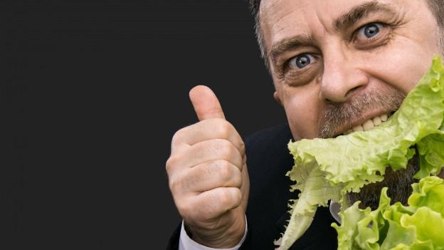 Mann isst Salat.