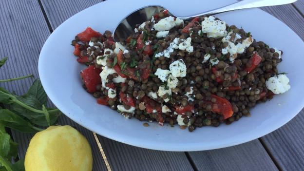 Linsensalat mit gschmorten Peperoni un Feta auf einem Teller.