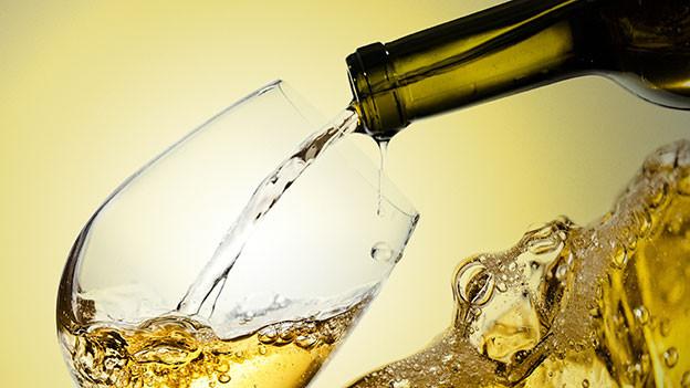 Ein Glas Weisswein wird eingeschenkt.