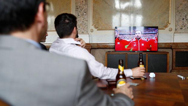 Nationalräte sitzen in einem Bundeshauszimmer vor einem TV. Es läuft Fussball.