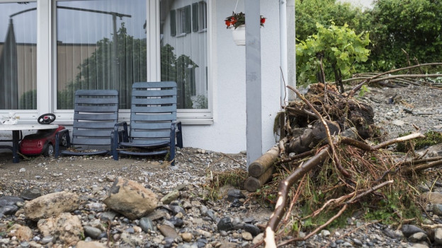 Hochwasser haben Schutt in den Garten vor ein Haus transportiert, der weggeräumt werden muss.