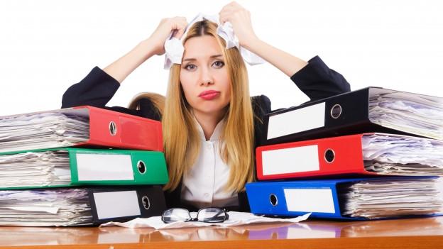 Frau im Büro viele Akten vor sich verzweifelt