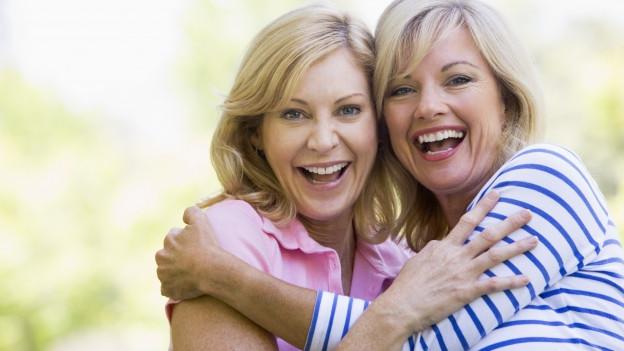 2 Frauen im mittleren Alter umarmen sich und lachen