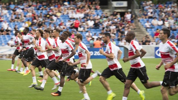 Die Spieler der Schweizer Fussball-Nationalmannschaft laufen in einer Reihe über ein Fussballfeld