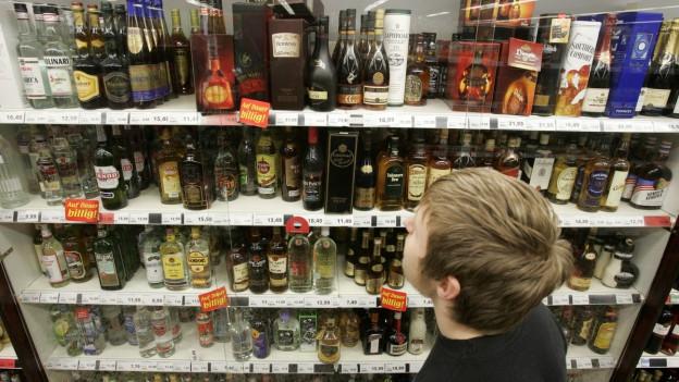 Ein Junge steht vor mehreren Regalen voll mit alkoholischen Getränken