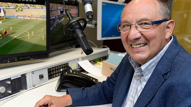 Beni Thurnheer vor einem Fernsehbildschirm.