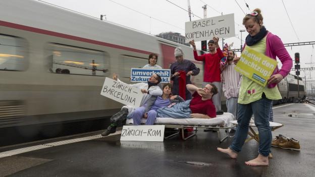 Ein Bahnperron, neben dem Zug stehen Protestierende mit Schildern grosser Hauptstädte, sie fordern weiterhin Nachtzüge.