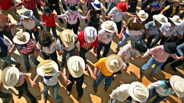 Frauen und Männer mit Cowboy-Hüten tanzen in einer Reihe.