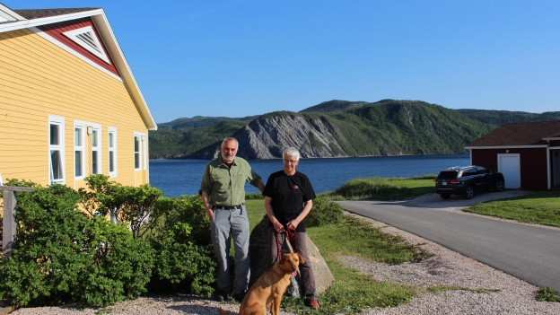 Bettina Lori, Herbert Schuhmacher und Labrador Retriever Nuka, postiert vor dem Neddies Harbour Inn. Im Hintergrund ist die Bonne Bay, ein Fjord.