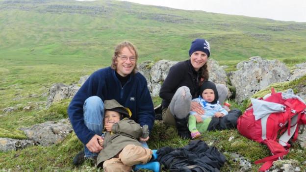 Christa Feucht und Martin Feucht sitzen mit ihren Kindern auf einem Felsen. Im Hintergrunde atemberaubende hügelige grüne Landschaft.