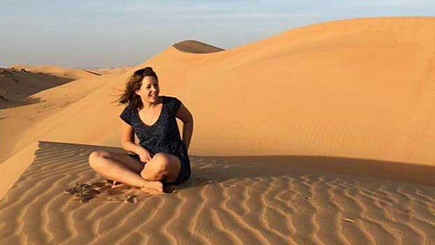 Nina Wachter sitzt auf einer Sanddüne in der Wüste.