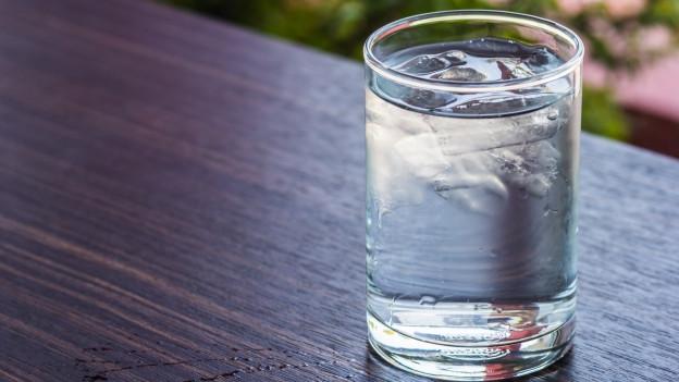 Ein Glas Wasser auf einem Tisch.