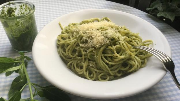 Basilikum-Pesto im Glas und ein Teller Pasta mit Pesto.