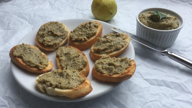 Geröstete Baguette-Scheiben mit Tapenade aus grünen Oliven bestrichen.