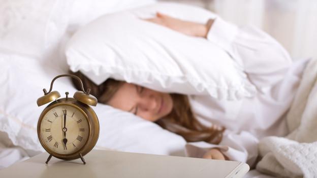 Wecker sechs Uhr Frau mit Kissen auf Kopf will nicht aufwachen