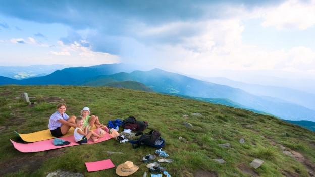 Mutter mit Kindern sitzt auf einem Berg beim Picknick, am Himmel hängen Wolken