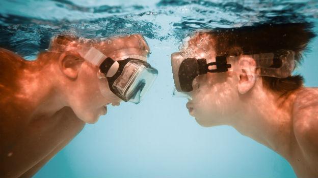 Zwei Knaben unter Wasser mit Tauchbrille.