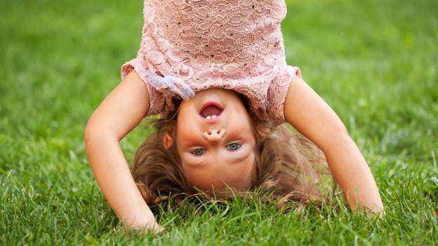 Ein kind macht den Purzelbaum.