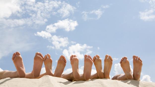 Fusssohlen von verschiedenen Leuten, die im Sand liegen