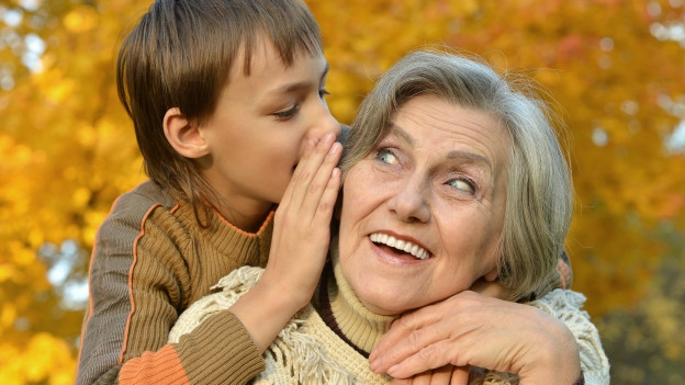 Ein Enkel flüstert seiner Grossmutter etwas ins Ohr.