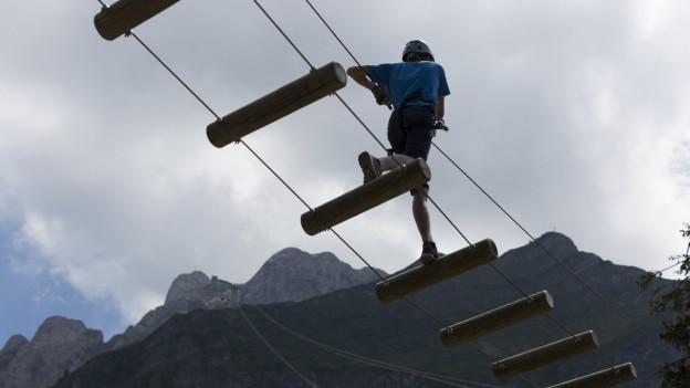 Eine Person klettert in einem Seilpark über eine hängende Leiter